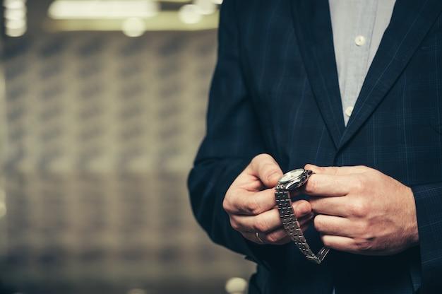 Um homem de negócios em um terno configura o tempo em um relógio de pulso.