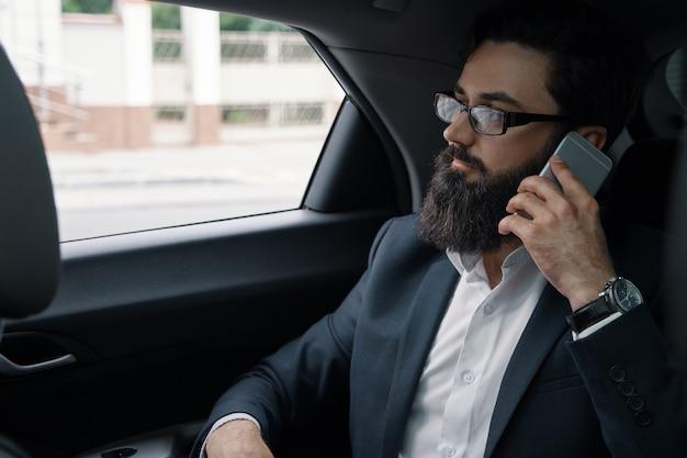 Um homem de negócios enquanto viaja de carro no banco de trás usando um smartphone