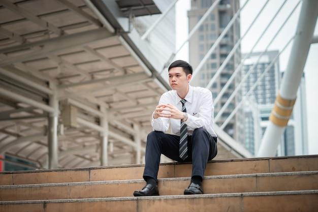Um homem de negócios está sentado na escada e pensando em algo.