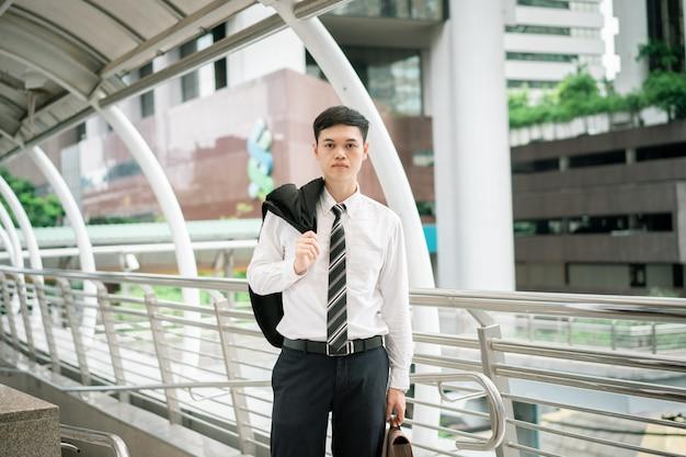 Um homem de negócios está vestindo um terno preto, camisa branca e gravata.