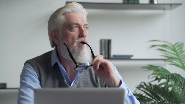 Um homem de negócios idoso pensativo com uma barba grisalha pensando na solução do problema trabalhando no laptop