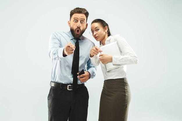 Um homem de negócios mostra o laptop para seu colega no escritório
