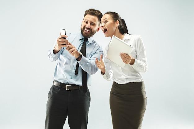 Um homem de negócios mostra o laptop para seu colega no escritório.