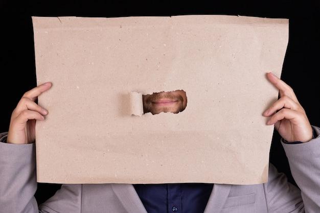 Um homem de negócios segura uma folha de papel com um orifício para a boca. conceito de censura. conceito de negócios.