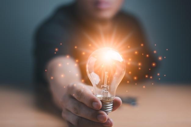 Um homem de negócios segurando a lâmpada de luz sucesso de salvar e manter o conceito, ideia de luz gráfica de computador