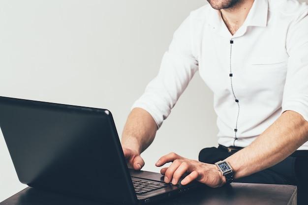 Um homem de negócios sitts na tabela e trabalha atrás de um portátil no escritório. um homem está digitando em um laptop uma mensagem