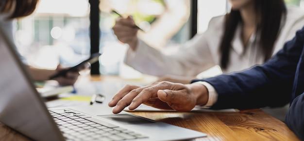 Um homem de negócios usa um laptop para ver as apresentações, a atmosfera de uma sala de reuniões de uma empresa iniciante com executivos e departamentos de vendas em uma reunião de planejamento. conceito de gestão de vendas.