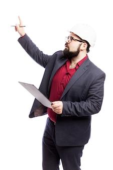 Um homem de óculos com uma barba em um capacete de construção branco e com um tablet na mão. vestido com um terno formal. isolado em uma parede branca vertical.
