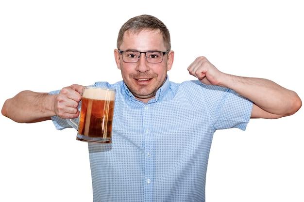 Um homem de óculos e camisa azul levanta alegremente o copo de cerveja. fundo branco isolado.