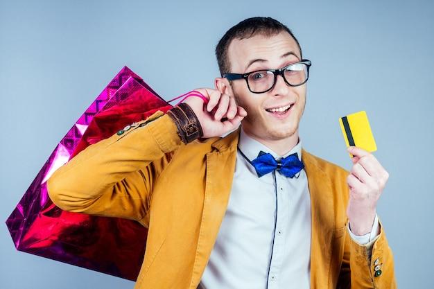 Um homem de óculos e um elegante terno amarelo guarda pacotes (bolsas) com compras e um cartão de crédito nas mãos. conceito de compras, generosidade e shoppoholism