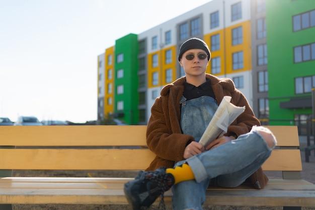 Um homem de óculos escuros está sentado em um banco