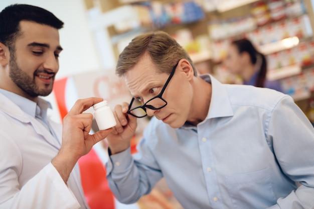 Um homem de óculos olha atentamente para o frasco de remédio.