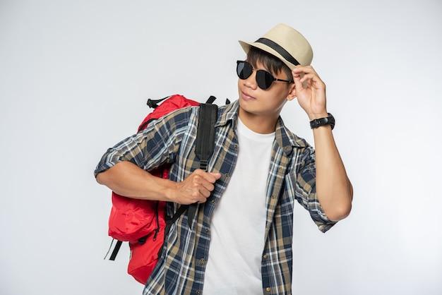 Um homem de óculos sai para viajar, usa um chapéu e carrega uma mochila