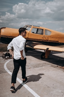 Um homem de pé no fundo de um avião pequeno monomotor.