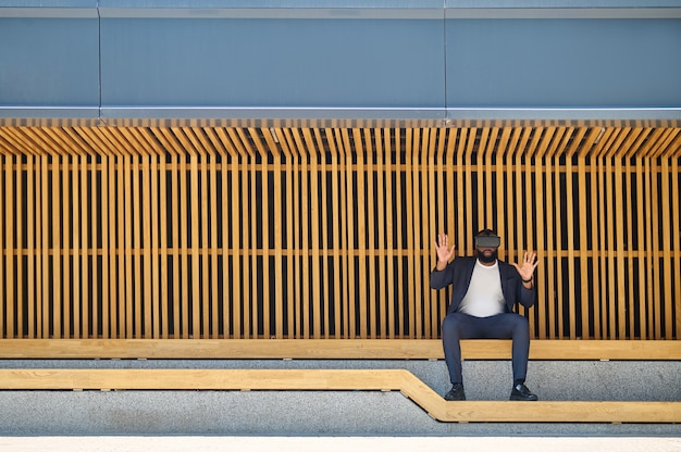 Um homem de pele escura com óculos vr sentado no banco