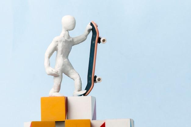 Um homem de plasticina branca está de pé em cima de cubos em um fundo azul e segurando um skate em uma mão. conceito de motivação, sucesso, realização do objetivo definido.
