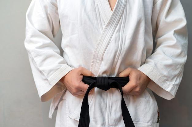 Um homem de quimono está segurando sua faixa preta e perto da parede de uma academia