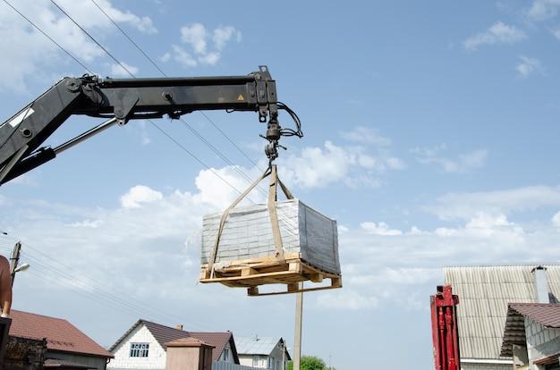 Um homem de raça europeia ajuda a carregar ladrilhos de um carro no chão. entrega e descarga de materiais de construção para a casa. guindaste de caminhão descarregado ladrilhos de rua.