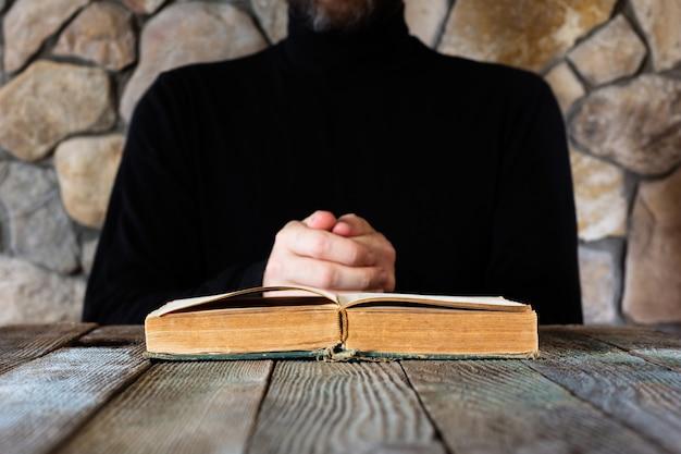 Um homem de roupas pretas em frente a um livro velho aberto