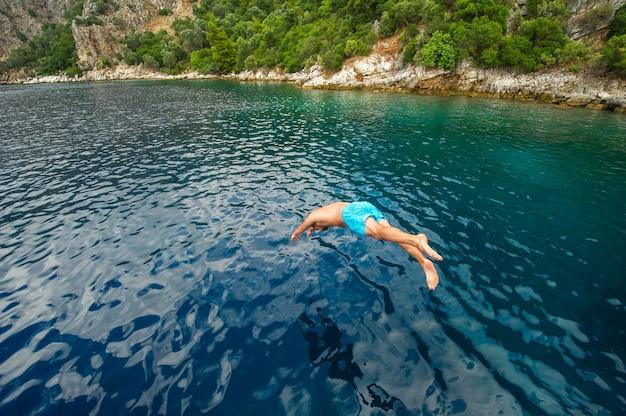 Um homem de short azul mergulha de um navio no mar perto da costa