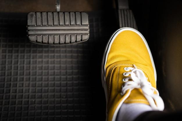 Um homem de tênis amarelos está pisando no acelerador de um carro.