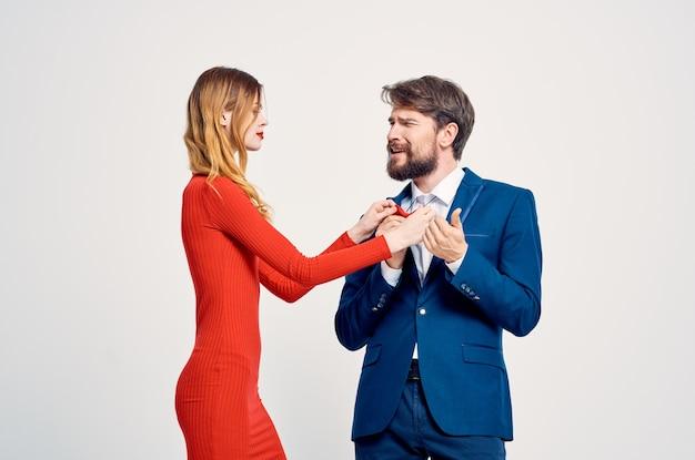 Um homem de terno ao lado de uma mulher com um vestido vermelho emoções gestos com as mãos fundo isolado