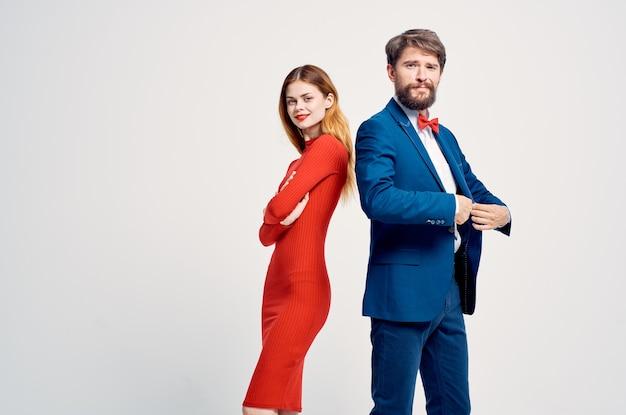 Um homem de terno ao lado de uma mulher em um vestido vermelho romance feliz fundo isolado