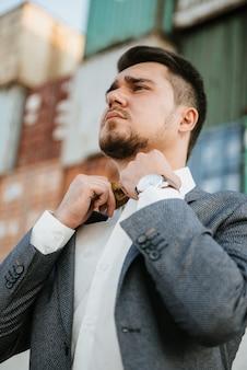 Um homem de terno cinza posa na rua para anunciar roupas masculinas. tiro para loja de roupas masculinas