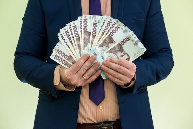 Um homem de terno com uma enorme pilha de dinheiro ucraniano. 1000 hryvnia. uah.