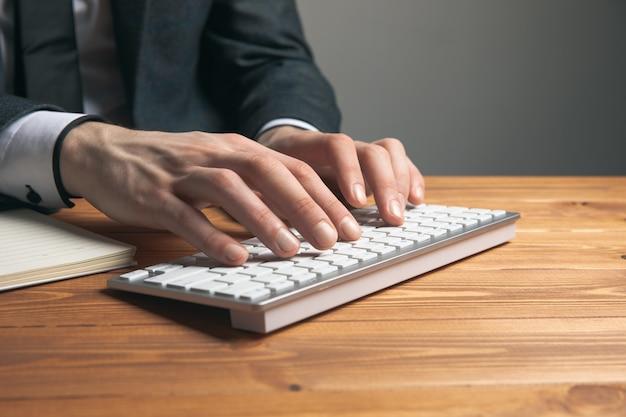 Um homem de terno escreve em um teclado em uma superfície cinza