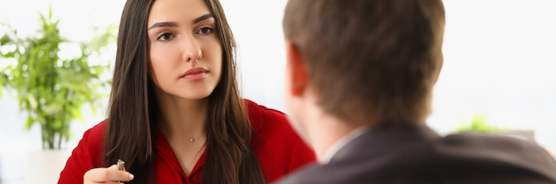 Um homem de terno está sentado em um escritório e conduz uma entrevista com uma jovem de roupas vermelhas