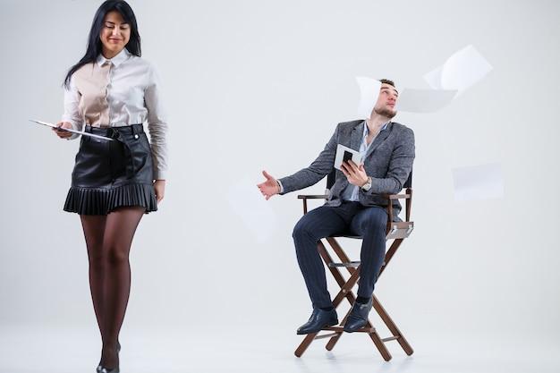Um homem de terno está sentado em uma cadeira preta com um tablet e uma mulher joga documentos. os futuros empresários estão nervosos e falando sobre um novo projeto. parceiros de negócios em um fundo branco.
