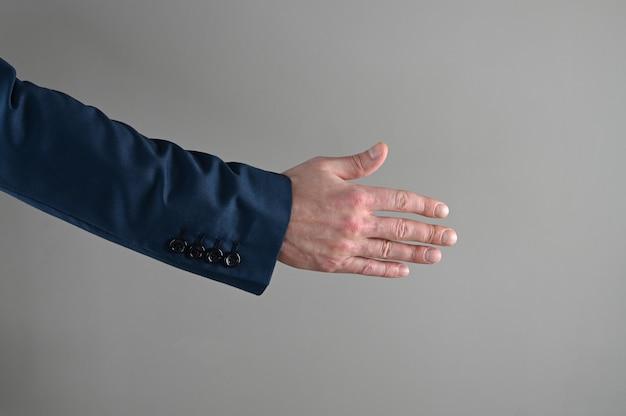 Um homem de terno estende a mão