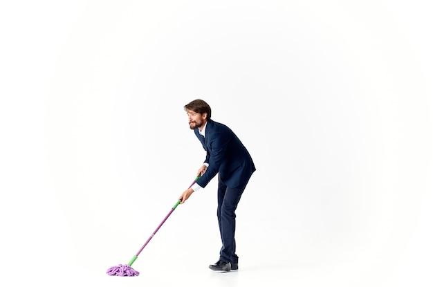 Um homem de terno lava o chão com um gerente de serviço de esfregão