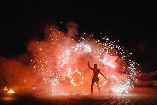 Um homem de terno led dança com noite de fogo