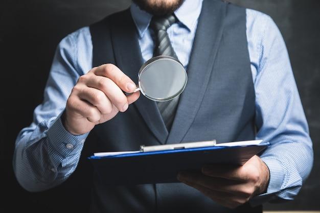 Um homem de terno olha documentos com uma lupa em um fundo cinza