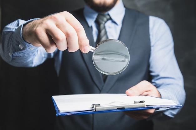 Um homem de terno olha documentos com uma lupa em uma parede cinza
