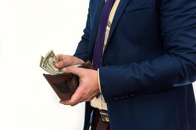 Um homem de terno olha em sua carteira e tira apenas $ 1. um empresário arruinado. o conceito de falência ou falência Foto Premium