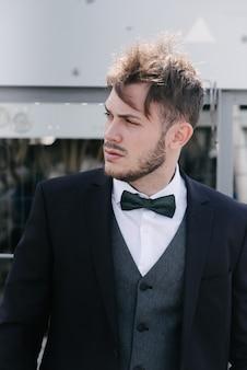 Um homem de terno preto e gravata-borboleta preta posa ao ar livre. anuncie roupas masculinas.