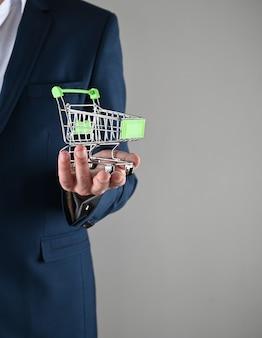 Um homem de terno segura um carrinho de compras nas mãos