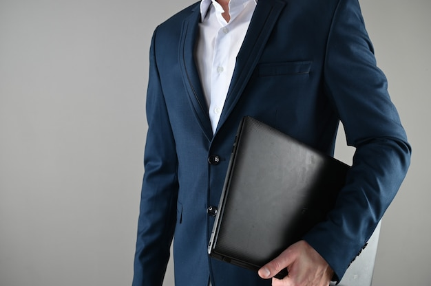 Um homem de terno segura um laptop nas mãos