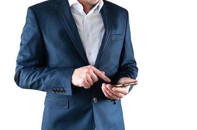 Um homem de terno segura um smartphone nas mãos