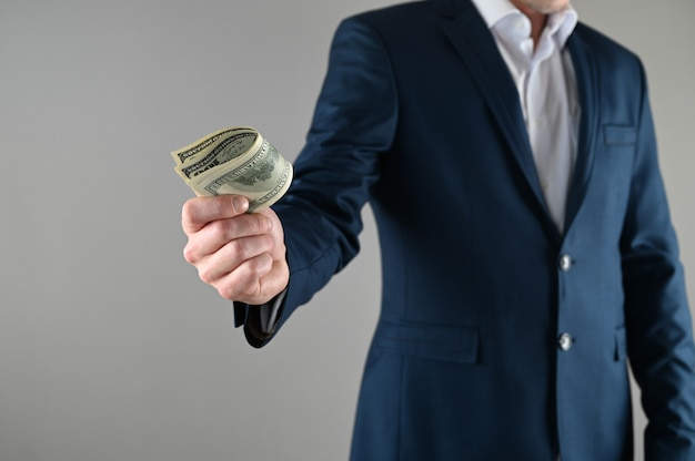 Um homem de terno tem dinheiro nas mãos