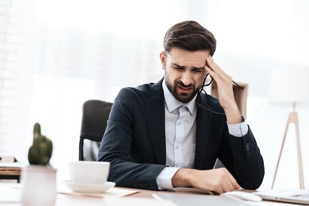 Um homem de terno tem uma dor de cabeça. ele mantém as mãos.