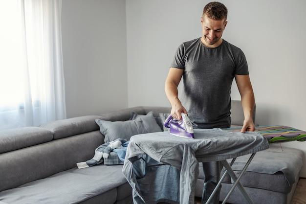Um homem de trinta e poucos anos passava roupas em uma tábua de passar na sala de estar