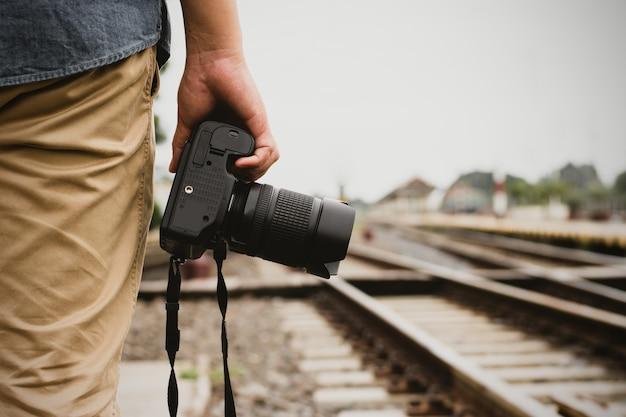 Um homem de turista em pé com uma câmera digital perto dos trilhos.