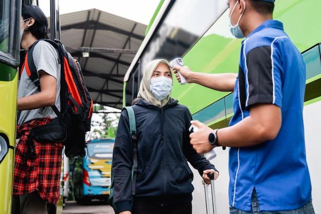 Um homem de uniforme e boné, usando uma pistola térmica, inspeciona o passageiro de uma mulher com lenço na cabeça e máscara antes de embarcar no ônibus
