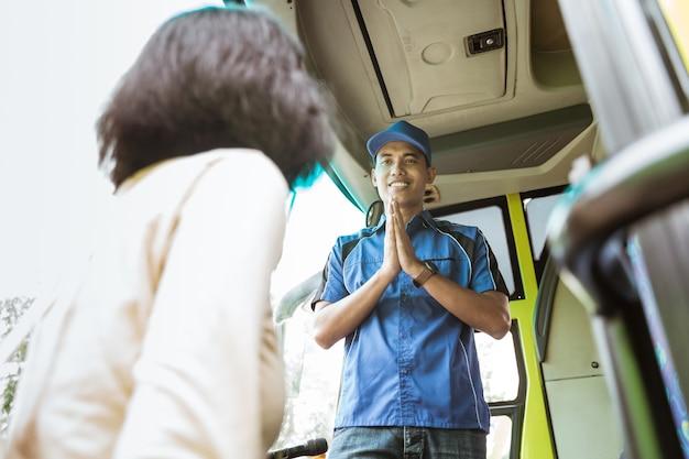 Um homem de uniforme e chapéu com um gesto de boas-vindas a uma passageira que entra no ônibus