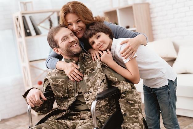 Um homem de uniforme em uma cadeira de rodas com sua família