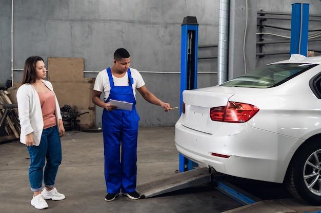Um homem de uniforme está conversando com um cliente em uma oficina mecânica